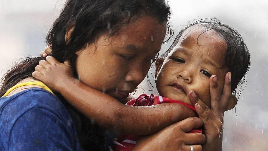 """Mulher segura uma criança em Tacloban, na ilha de Leyte, Filipinas. Milhares de sobreviventes sofrem com a escassez de alimentos e água após a passagem do supertufão """"Haiyan"""" na última sexta-feira (07/11)"""