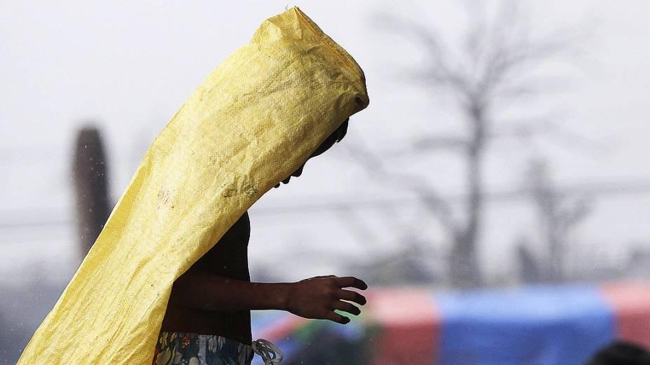 """Menino cobre a cabeça enquanto caminha na chuva pelas ruas de Tacloban, na ilha de Leyte, Filipinas. Milhares de sobreviventes sofrem escassez de alimentos e água após a passagem do supertufão """"Haiyan"""" na última sexta-feira (07)"""