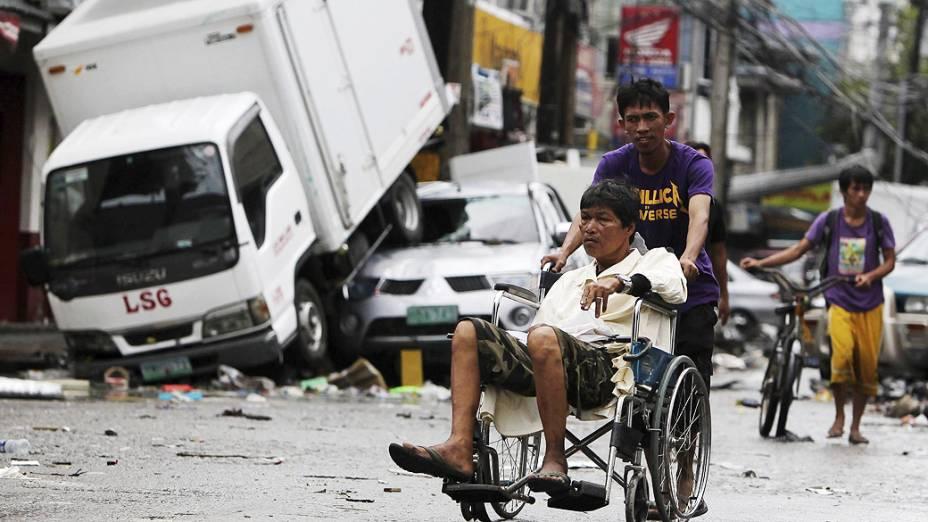 """Pedestres caminham pelas ruas de Tacloban, na ilha de Leyte, Filipinas. Milhares de sobreviventes sofrem escassez de alimentos e água após a passagem do supertufão """"Haiyan"""" na última sexta-feira (07/11)"""