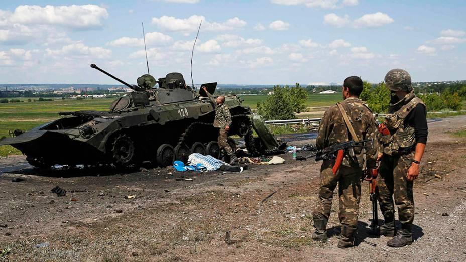 Soldados ucranianos inspecionam um tanque destruído usado por rebeldes pro-Rússia, em Slaviansk na Ucrânia