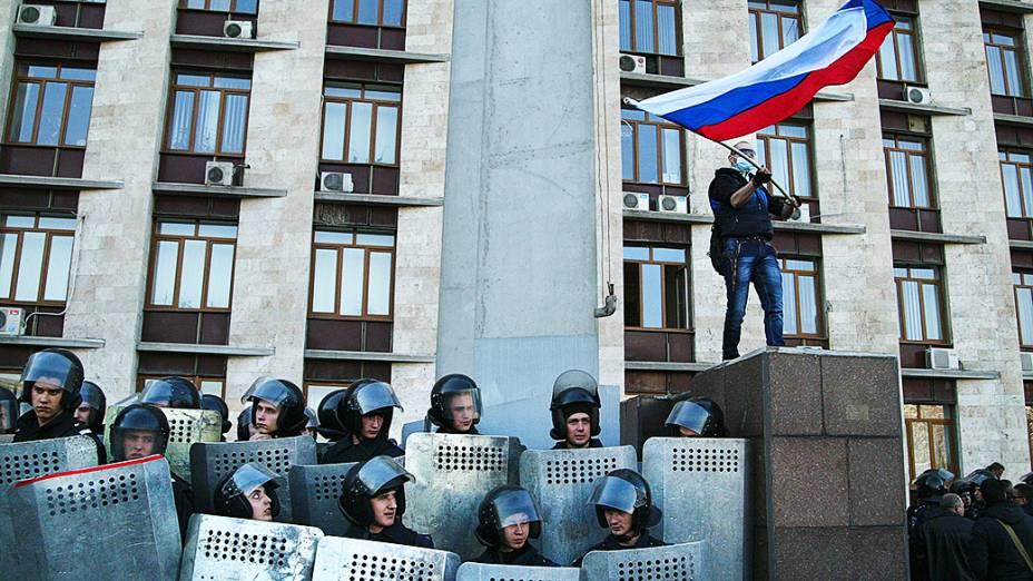 Observado por policiais ucranianos, homem mascarado balança bandeira russa diante de prédio da administração regional de Donetsk, no leste da Ucrânia
