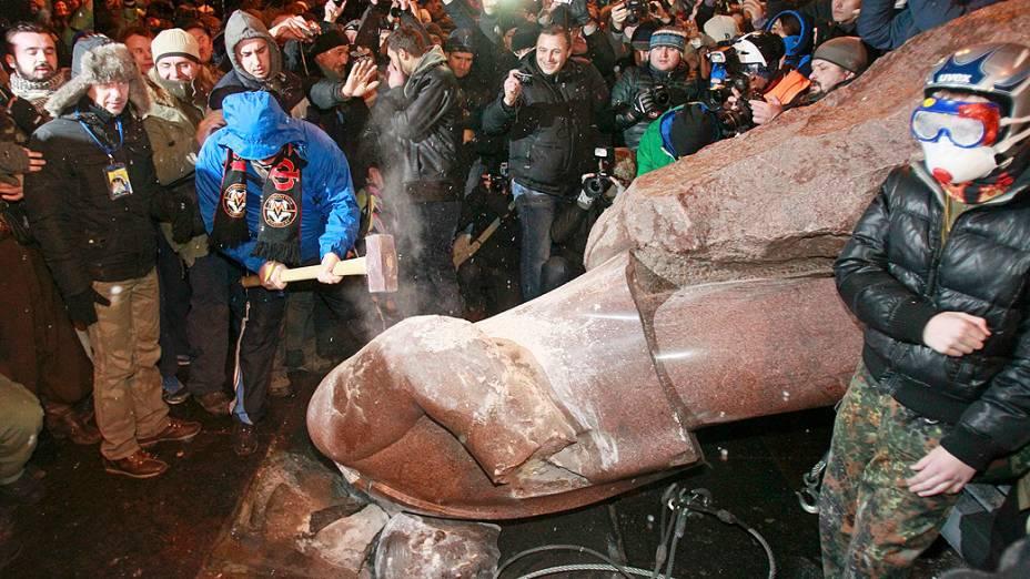 Homem destrói a marteladas uma estátua do fundador do Estado soviético Vladimir Lenin, derrubada por manifestantes pró União Europeia, em Kiev