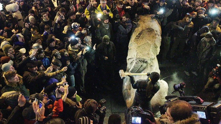 Homem destrói a marretadas uma estátua do fundador do Estado soviético Vladimir Lênin, derrubada por manifestantes pró União Europeia, em Kiev durante um protesto chamado A Marcha do Milhão