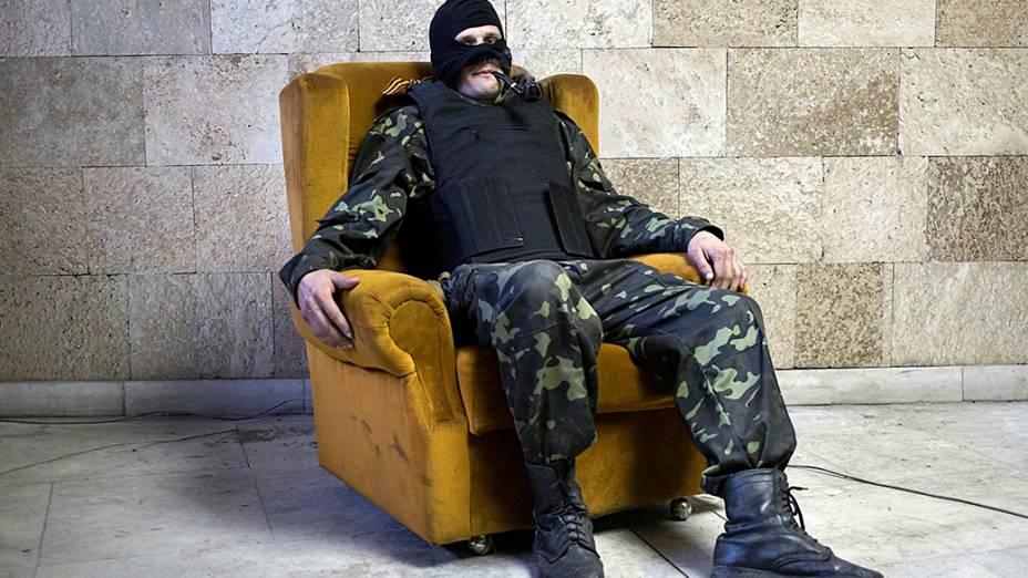 Fumando cachimbo, militante pró-Rússia posa para foto dentro de prédio ocupado em Donetsk, leste da Ucrânia