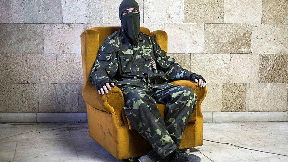 Militante pró-Rússia mascarado posa para uma foto dentro de um prédio do governo regional em Donetsk, leste da Ucrânia