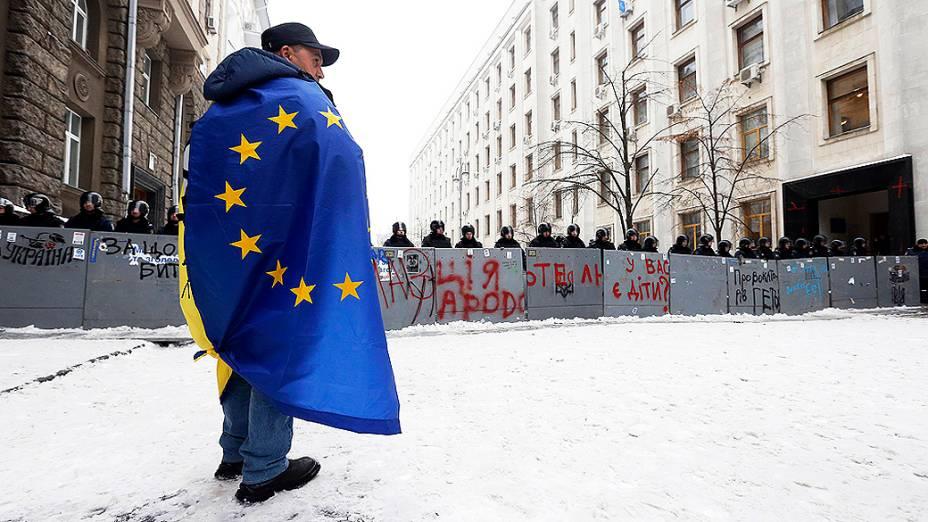 Manifestante com uma bandeira da União Européia nos ombros fica na frente de um bloqueio policial no centro de Kiev, na Ucrânia