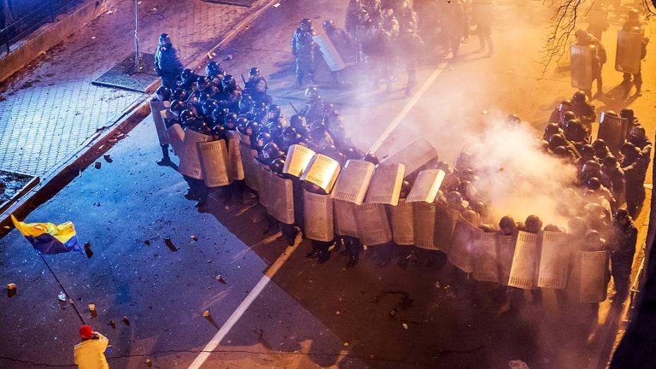 Manifestante segura a bandeira da Ucrânia em frente a um grupo de policiais durante protesto contra a decisão do presidente, Viktor Yanukovych, de suspender um acordo comercial com a União Europeia em frente à sede do governo, em Kiev