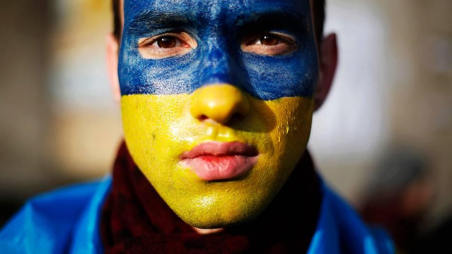 Manifestante com o rosto pintado com as cores da bandeira ucraniana posa para um retrato na Praça da Independência, em Kiev