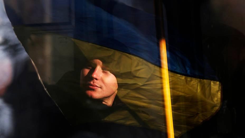 A bandeira ucraniana segurada por manifestantes é refletida no rosto de um policial que faz a segurança do prédio do governo em Kiev