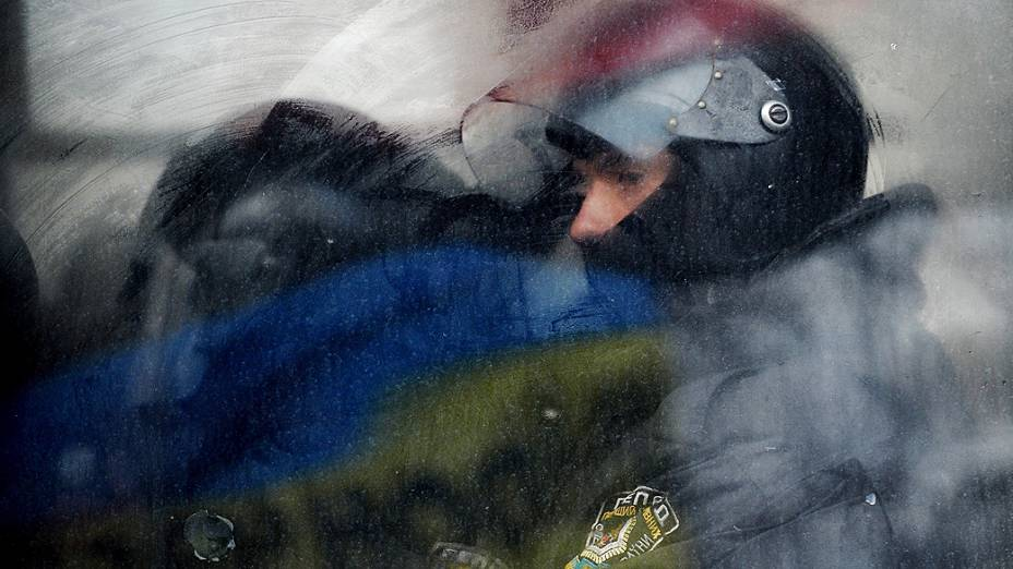 Policial observa de dentro de um ônibus, um bloqueio realizado por manifestantes durante protesto em Kiev