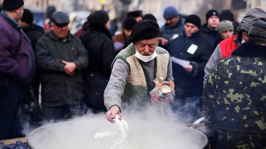 Homem prepara refeição para os manifestantes que se estabeleceram na Praça da Independência, em Kiev em protesto à decisão do presidente ucraniano, Viktor Yanukovych, de suspender um acordo comercial com a União Europeia