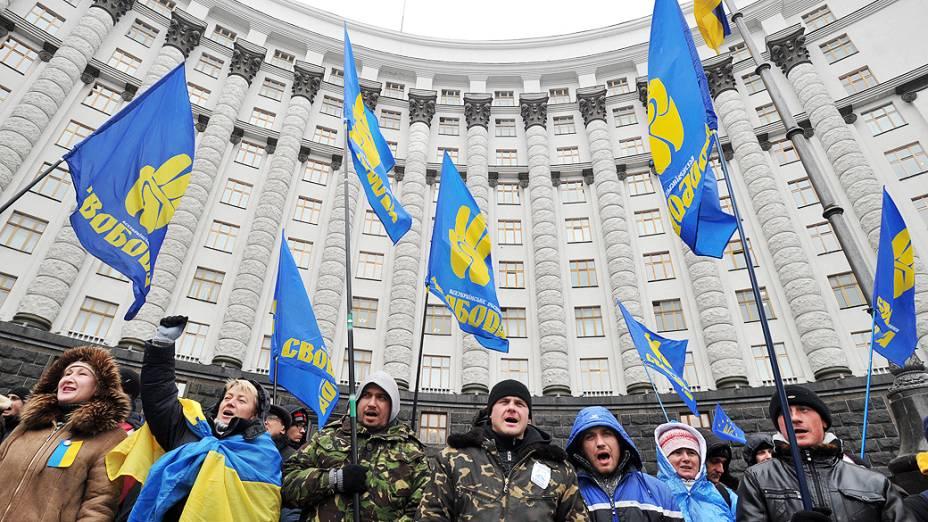 Manifestantes pró-União Europeia, seguram bandeiras do partido de oposição Svoboda, cantam mensagens de protesto e bloqueiam a entrada para o prédio do governo em Kiev