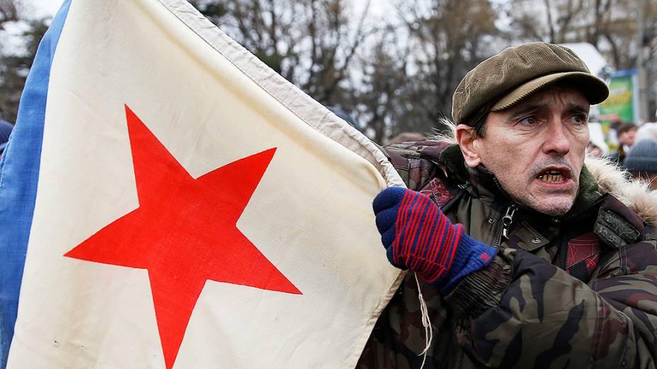 Homem segura uma bandeira militar da era soviética durante um comício pró-Rússia em Simferopol, na região da Crimeia