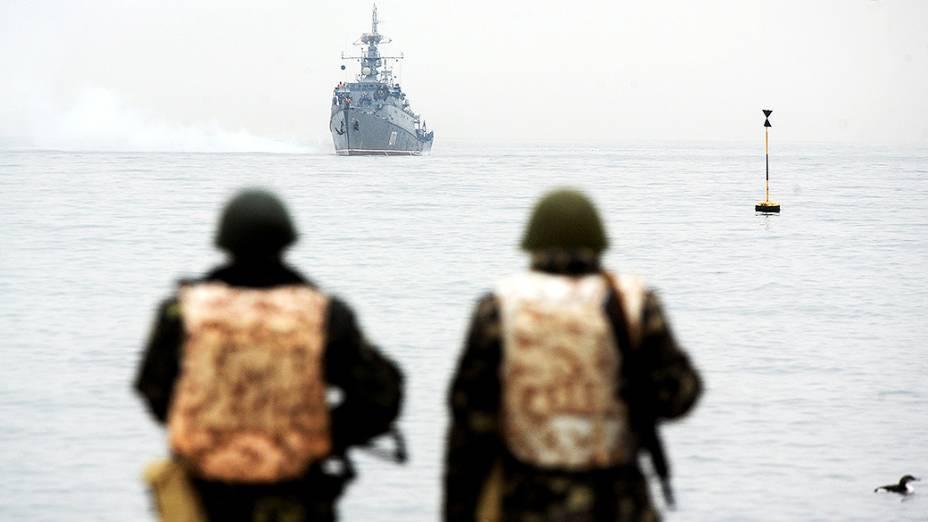 Integrantes da marinha ucraniana observam um navio russo posicionado na baía de Sebastopol, na região da Crimeia