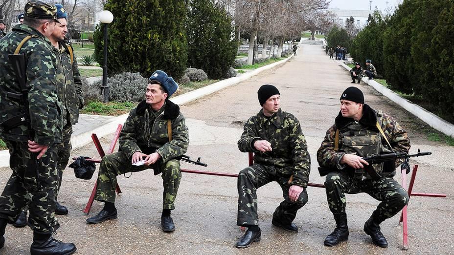 Pilotos da força aérea ucraniana montam guarda na base aérea militar em Belbek, perto de Sebastopol, que está cercada por forças russas