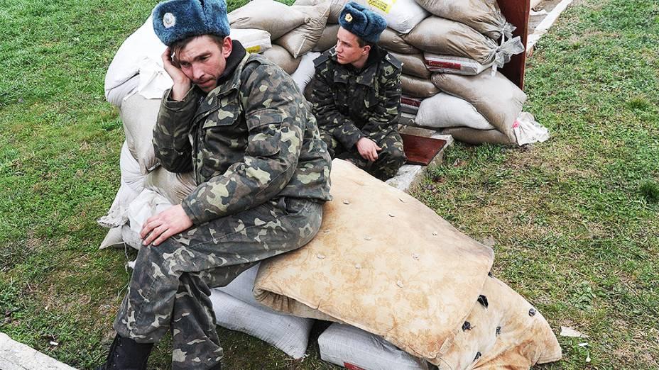 Pilotos da força aérea ucraniana sentados em sacos de areia na base aérea militar em Belbek, perto de Sebastopol, que está cercada por forças russas