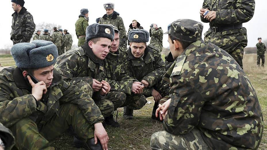 Soldados ucranianos descansam perto da entrada da base aérea de Belbek na periferia de Sebastopol, na Crimeia