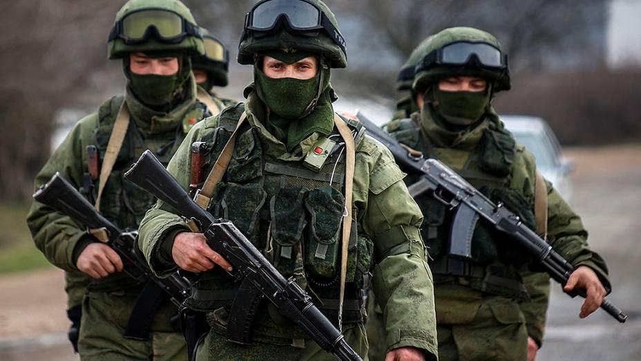 Homens armados, supostamente militares russos, marcham fora de uma base militar ucraniana na aldeia de Perevalnoye perto da cidade de Simferopol, na região da Crimeia