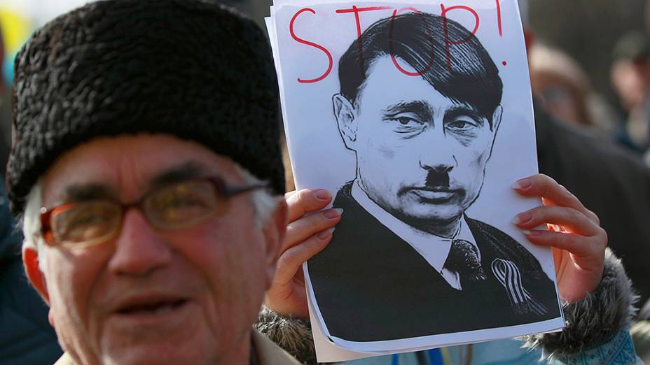 Manifestante pró-Ucrânia segura um retrato do presidente russo Vladimir Putin com referência a Adolf Hitler, durante um comício na cidade Simferopol na região da Crimeia