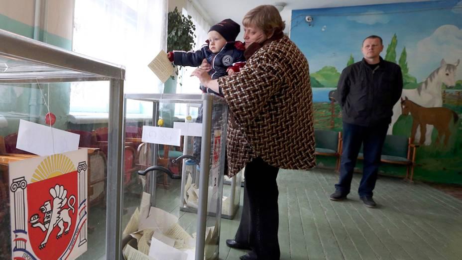 Criança segura o voto do referendo que decidirá se a Crimeia deve ou não se separar da Ucrânia