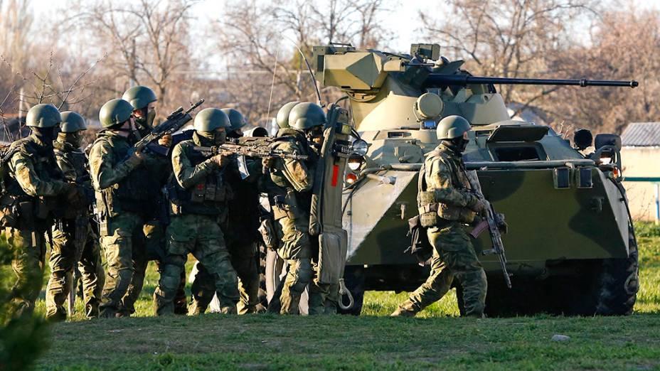 Soldados supostamente russos, se protegem atrás de um blindado, enquanto tentam invadir a base aérea de Belbek, na Crimeia