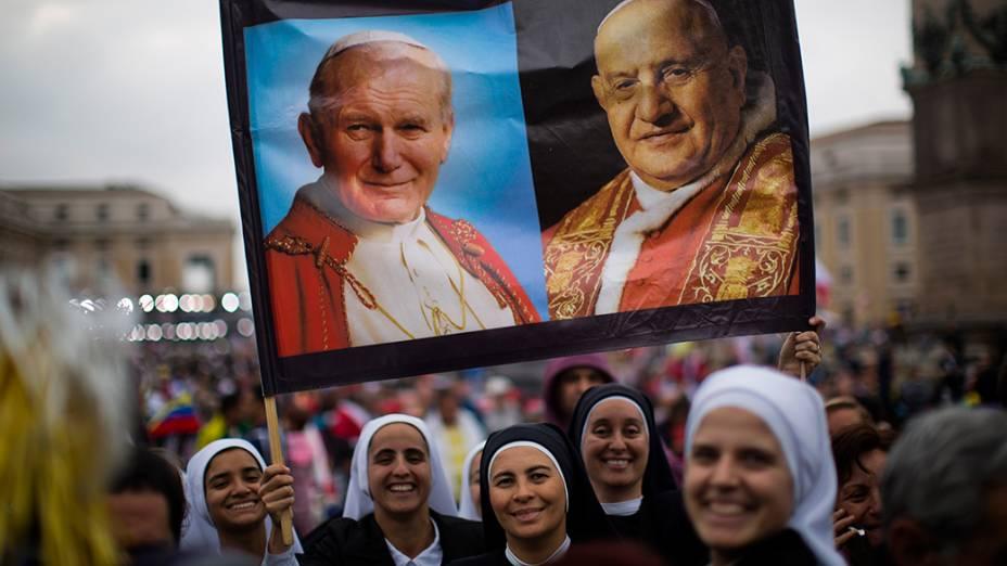 Freiras seguram cartazes com as fotografias de João Paulo II e João XXIII que foram proclamados santos pela Igreja Católica