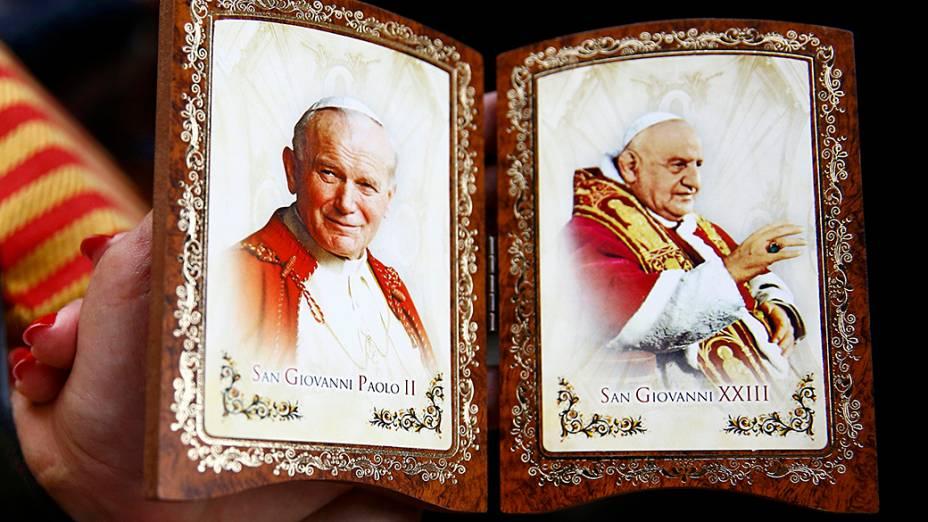 Fiel segura souvenir com as imagens dos papas João XXIII e João Paulo II, canonizados neste domingo (27)