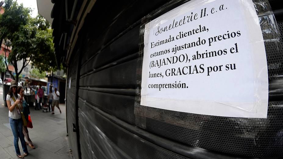 Aviso do lado de fora de uma loja de aparelhos eletrônicos anuncia seu fechamento temporário para ajuste de preços, em Caracas