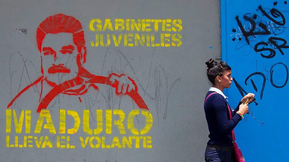 """Mulher passa por um mural com desenho do presidente interino Nicolás Maduro """"ao volante"""", em Caracas"""
