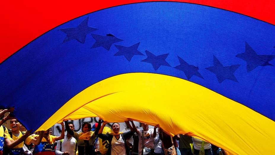 Partidários da oposição seguram uma grande bandeira nacional durante protesto em Caracas, em 21/03/2013