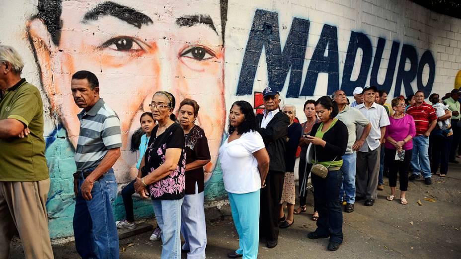 Pessoas fazem fila para votar em Petare, Caracas, diante da propaganda chavista