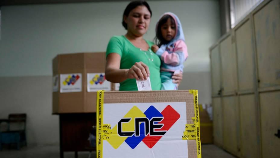 Mulher deposita seu voto em uma sessão eleitoral na favela Petare, em Caracas