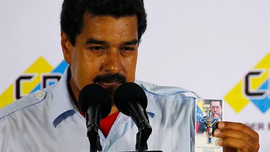 Nicolas Maduro segura lembrança religiosa com uma imagem do falecido presidente Hugo Chávez durante coletiva de imprensa no comitê eleitoral em Caracas neste domingo (14)