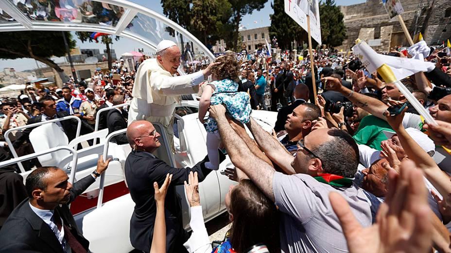 Papa Francisco toca uma criança em meio a multidão de fiéis na Praça da Manjedoura, em Belém, na Cisjordânia