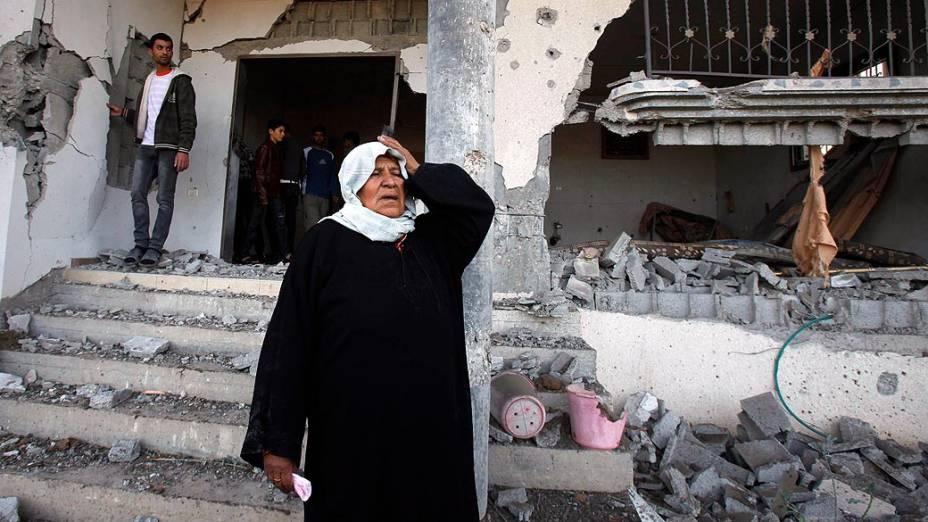 Mulher vê sua casa destruída após ataque aéreo na Faixa de Gaza