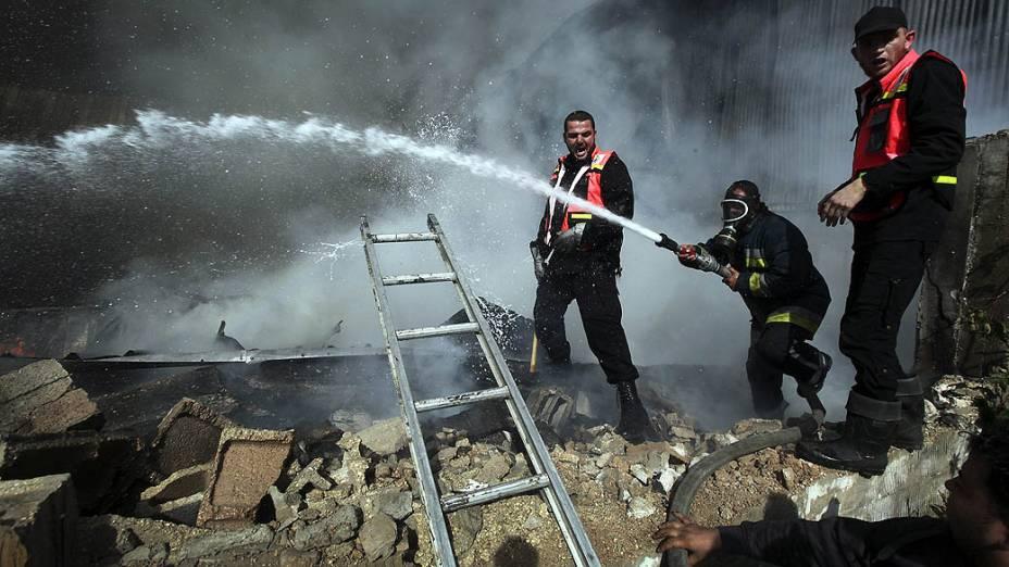Bombeiros palestinos apagam incêndio causado por ataque aéreo, em Jabaliya, norte da Faixa de Gaza
