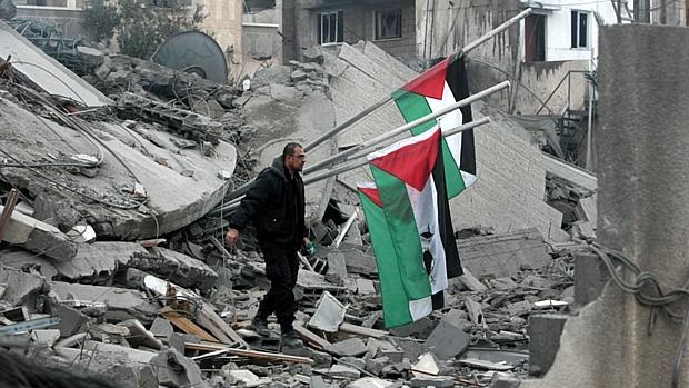 Palestino caminha sobre destroços da sede do Hamas, bombardeada por mísseis israelenses