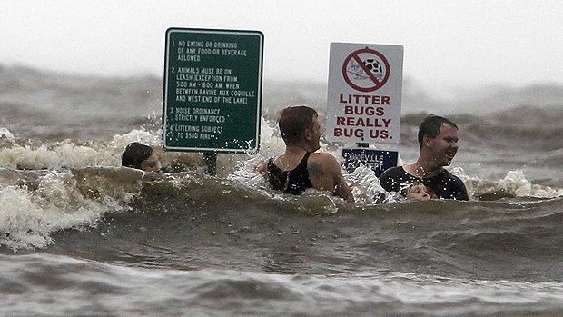 Jovens nadam em uma rua inundada ao lado do lago Pontchartrain, em Mandeville, na Louisiana (EUA), após a passagem do furacão Isaac pelo Estado