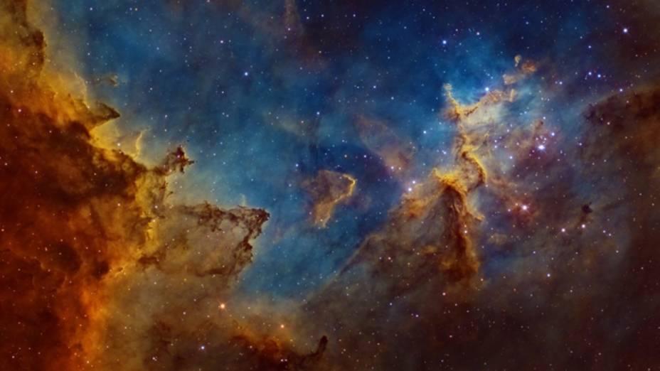 <p>A 7.500 anos-luz de distância da Terra se localiza a Nebulosa do Coração, uma vasta região de gases brilhantes energizados por um conjunto de  estrelas jovens em seu centro. A imagem destaca a região central, onde as nuvens de poeira são moldadas pela radiação cósmica</p>