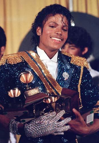 Carregando prêmios de diversas categorias, o astro deixa o Grammy de 1984 com uma jaqueta brilhante azul