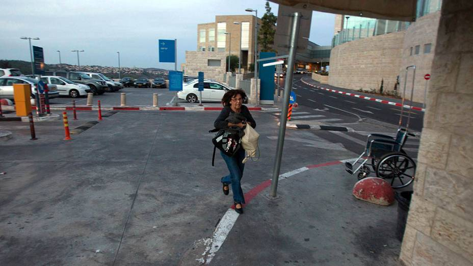 Mulher corre para se proteger após ouvir sirenes de alerta, em Jerusalém