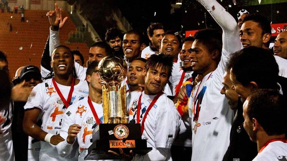 Neymar segura taça e jogadores do Santos comemoram após vencer jogo contra o Universidad del Chile