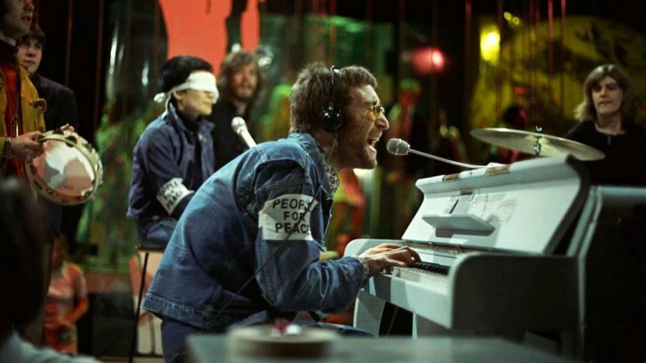 John Lennon e Yoko Ono, ao fundo vendada, participam do programa <em>Top of the Pops</em> em fevereiro de 1970