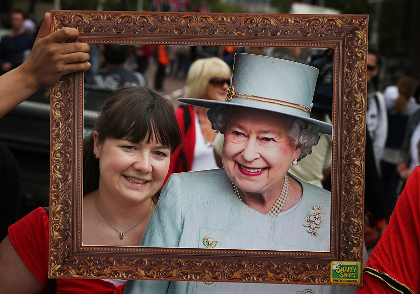 Mulher fotografada com banner da rainha Elizabeth II em The Mall próximo ao Palácio de Buckingham em Londres, Inglaterra. Dois dias antes do início das celebrações do Jubileu de Diamante