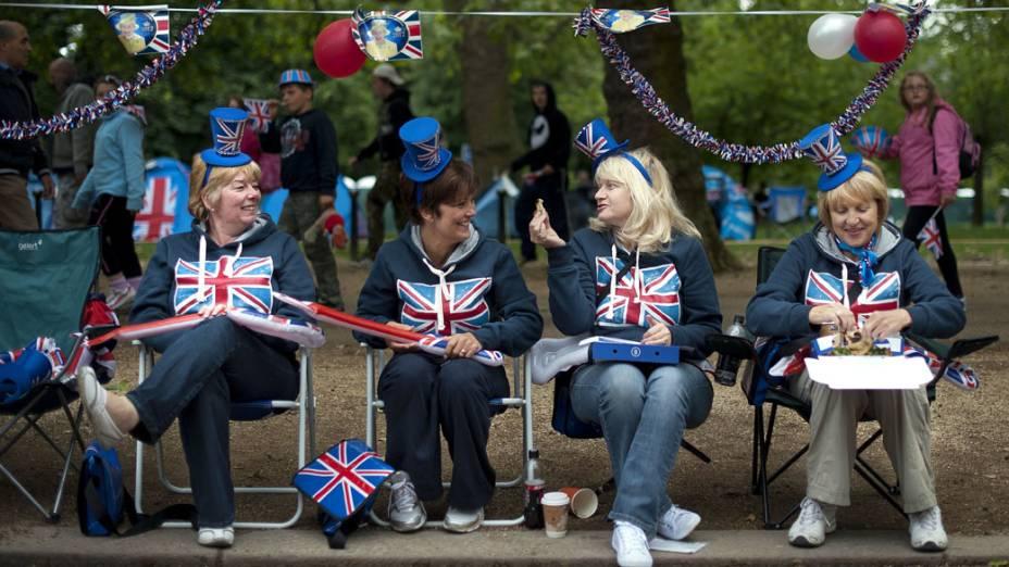 Mulheres aguardam show na parte externa do Palácio de Buckingham, em Londres