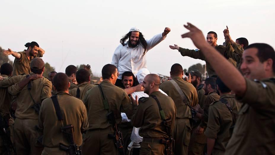 Judeu hassídico membro da seita Breslov, é carregado por um soldado israelense durante uma visita às tropas, perto da fronteira com a Faixa de Gaza