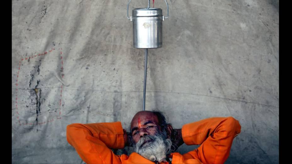 Sadhu, ou homem sagrado hindu descansa próximo às margens do Ganges em Allahabad, Índia