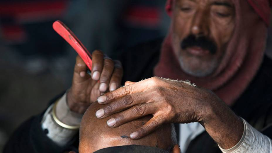 Barbeiro raspa a cabeça de devoto hindu no festival Kumbh Mela realizado às margens do Rio Ganges