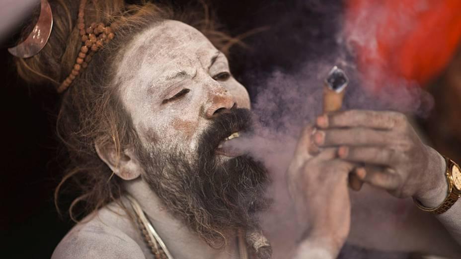 Hindu sagrado fuma às margens do Rio Ganges