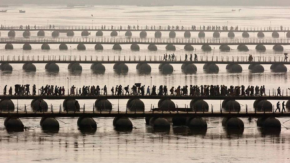 Devotos hindus atravessam o Rio Ganges em pontes flutuantes na cidade de Allahabad, norte da Índia